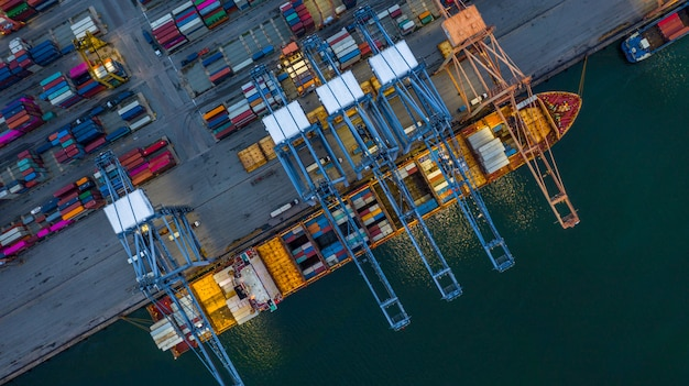 Aerial view container ship loading at night in industrial port. Premium Photo