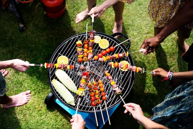 Vista aerea di un gruppo eterogeneo di amici grigliare barbecue all'aperto Foto Gratuite