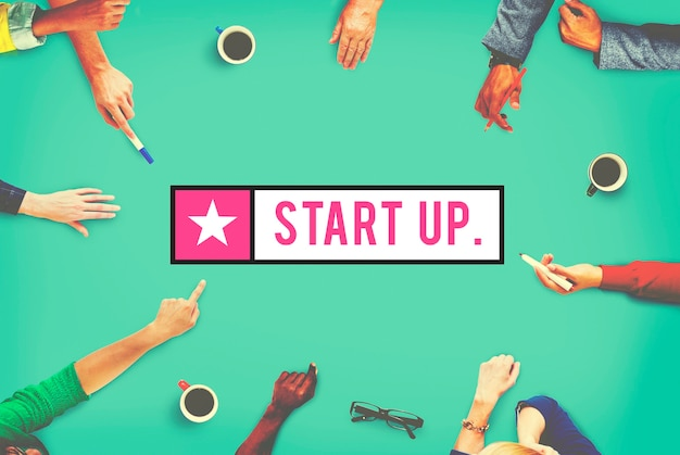 Aerial view of diverse hands pointing to startup word Free Photo