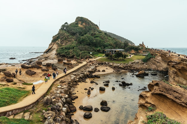 Aerial view diversity of tourists walking in yehliu geopark, a cape on the north coast of taiwan. a landscape of honeycomb and mushroom rocks eroded by the sea. Premium Photo