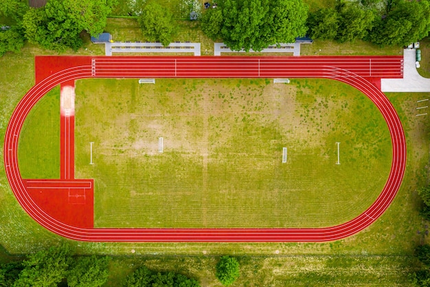 Aerial view of empty green football field and red running tracks, race track in a opened stadium. Premium Photo
