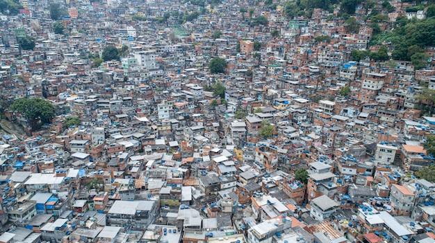 Aerial view of favela da rocinha, biggest slum in brazil on the mountain in rio de janeiro, and skyline of the city behind Premium Photo