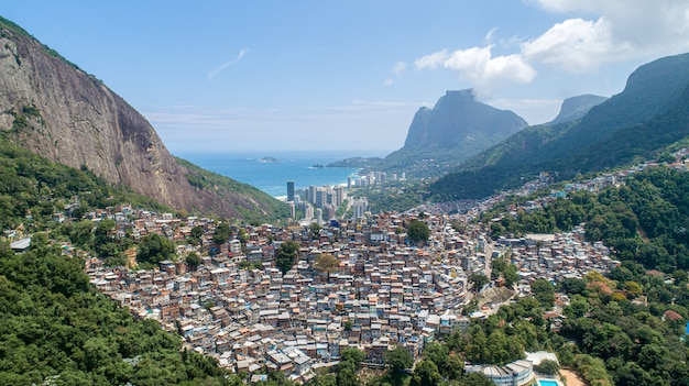 Aerial view of favela da rocinha, biggest slum in brazil on the mountain in rio de janeiro, and skyline of the city behind Premium Photo