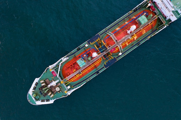 Aerial view of gas storage tank on ship in port, refinery industry and export cargo ship Premium Photo