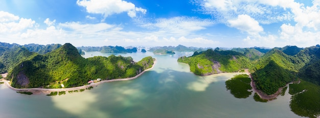 Aerial view of ha long from bay cat ba island, unique limestone rock islands and karst formation peaks in the sea, famous tourism destination in vietnam. scenic blue sky. Premium Photo