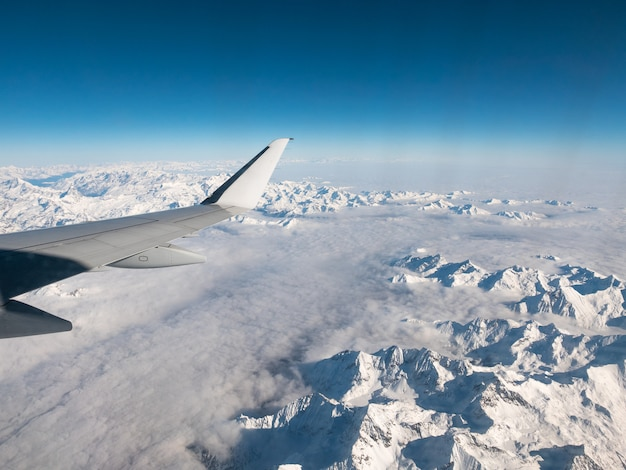 Aerial view of the italian swiss alps in winter, with generic aeroplane wing. snowcapped mountain range and glaciers. expansive view, clear blue sky. Premium Photo