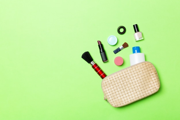 Aerial view of a leather cosmetics bag with make up beauty products spilling out on green background Premium Photo