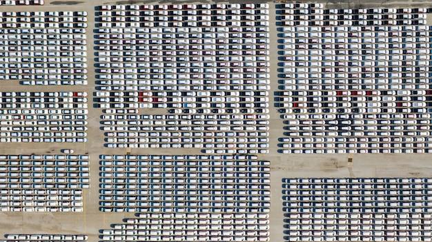 空撮輸出用、ビジネス用、物流用の新しい車の駐車場にたくさんの車 Premium写真