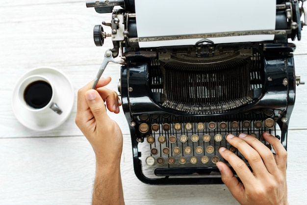 Aerial view of a man typing on a retro typewriter blank paper Free Photo