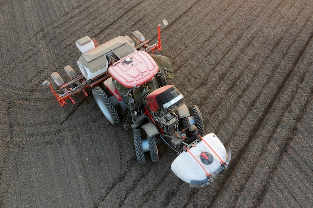 Aerial view of a modern multifunctional tractor, fertilizing pesticides, herbicides and sowing the area at the same time. Premium Photo