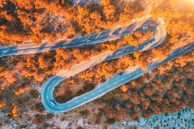 Aerial view of mountain curve road with cars, orange forest at sunset in autumn Premium Photo