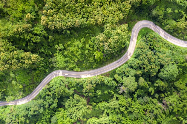 Aerial view over mountain road going through tropical rainforest landscape in thailand. Premium Photo