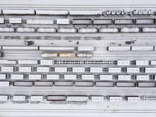 Witerの貨物列車の航空写真。駅で雪に覆われた貨物列車。重工業。無人。 Premium写真