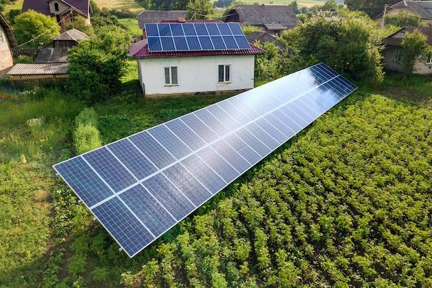 クリーンエネルギーのための青い太陽電池パネルが付いている家の空撮。 Premium写真