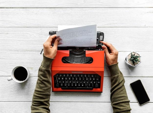 Аэрофотосъемка человека, набравшего на пишущей машинке ретро Бесплатные Фотографии