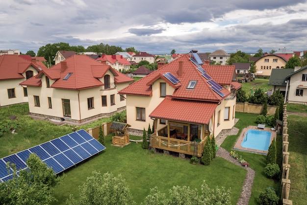 屋根にソーラーパネルと温水ラジエーターを備えた新しい自立型住宅と青いプールのある緑の庭の空撮。 Premium写真