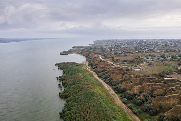 美しい砂丘と緑の海岸のある巨大な湖に沿った小道の空撮 無料写真