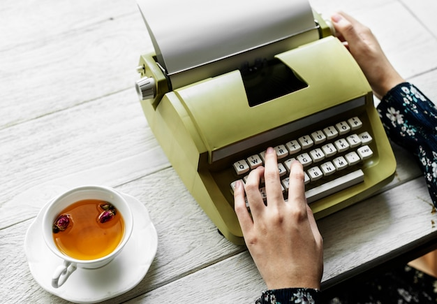 Аэрофотосъемка женщины, печатающей на пустой бумаге ретро-пишущей машинки Бесплатные Фотографии