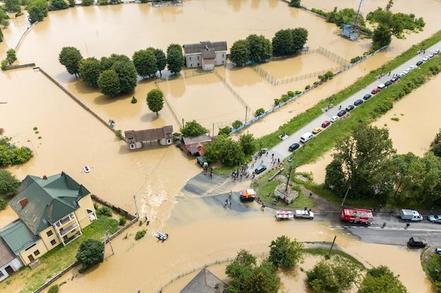 ウクライナ西部のハリチの町で水没した家屋と救助車の空撮。 Premium写真