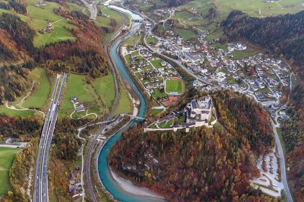 Вид с воздуха зеленых лугов с деревнями и леса в горах альпов австрийца. Premium Фотографии