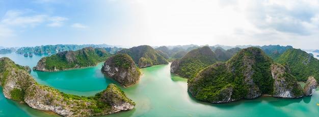 Аэрофотоснимок острова халонг бэй-бэй, уникальных островов известковой скалы и карстовых пиков в море, известного туристического направления во вьетнаме. живописное голубое небо. Premium Фотографии