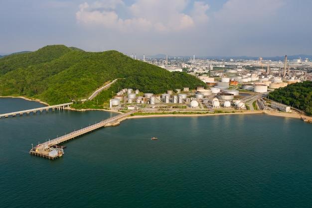 Вид с воздуха на большие резервуары для хранения топлива в промышленной зоне нефтеперерабатывающего завода и море с мостом на переднем плане в таиланде Premium Фотографии