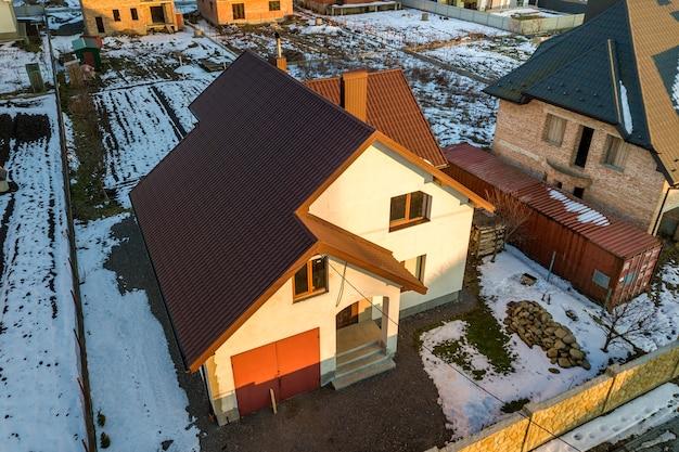 新しい住宅のコテージとモダンな郊外の晴れた冬の日にフェンスで囲まれた庭に帯状疱疹の屋根が付いている付属のガレージの空撮。ドリームハウスへの完璧な投資。 Premium写真