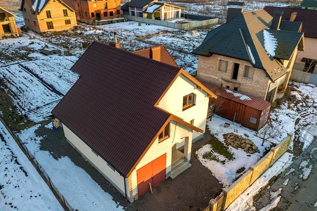 新しい住宅のコテージとモダンな郊外の晴れた冬の日にフェンスで囲まれた庭に帯状疱疹の屋根が付いている付属のガレージの空撮。 Premium写真