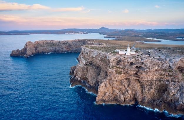 Вид с воздуха на маяк пунта-нати на менорке на вершине высоких скал у моря Premium Фотографии