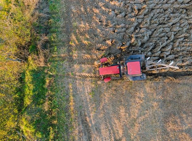 日没の夕方に秋の赤いトラクターの耕作地の空撮。 Premium写真