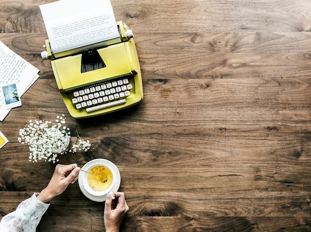 Аэрофотосъемка ретро-пишущей машинки и женщина с чашкой чая Бесплатные Фотографии