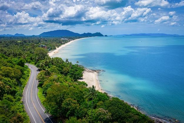Вид с воздуха на дорогу между кокосовой пальмой и великим океаном в дневное время в накхонситхаммарат, таиланд Premium Фотографии