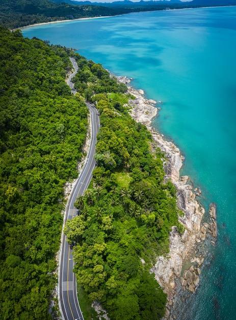 タイ、ナコンシータンマラートの昼間のココヤシの木と大海原の間の道路の航空写真 Premium写真