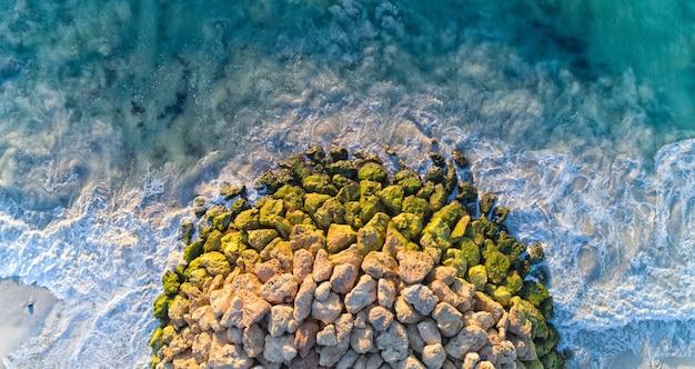 昼間の日光の下で波状の海に囲まれた互いの岩の空撮 無料写真