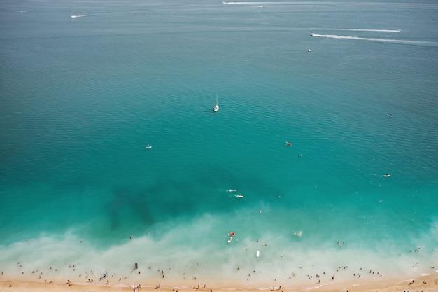 Аэрофотоснимок песчаного пляжа с туристами, купание в красивой чистой морской воде и яхте с видом сверху. Premium Фотографии