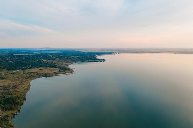 Аэрофотоснимок живописного ландшафта земли, деревья, небо отражается в воде. Бесплатные Фотографии