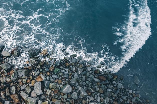 岩に砕ける海の波の空撮 無料写真