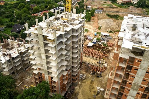 Аэрофотоснимок башенного подъемного крана и бетонный каркас строящихся многоквартирных жилых домов в городе Premium Фотографии