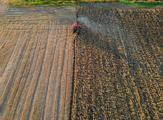 トラクターの空撮は、日没の夕方に畑の秋を耕します。 Premium写真