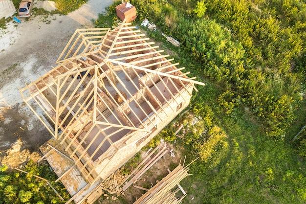 건설중인 목조 지붕 구조와 미완성 된 벽돌 집의 공중 전망. 프리미엄 사진