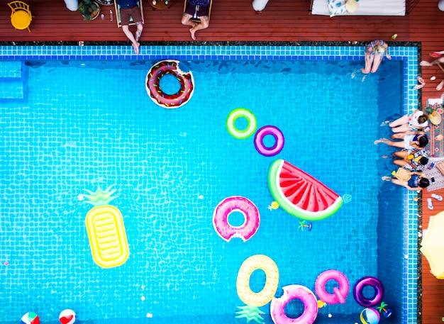 Aerial view of people enjoying the pool with colorful inflatable floats Free Photo