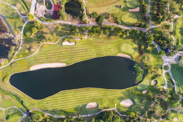 Aerial view photography of forest and golf course with lake. golf and sport club. Premium Photo