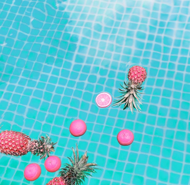 Aerial view of pineapple and oranges floating in a swimming pool Free Photo