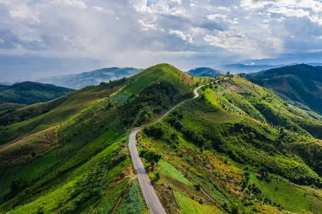 Aerial view road way on the green mountain peak in the rain season and morning mist and blue sky Premium Photo