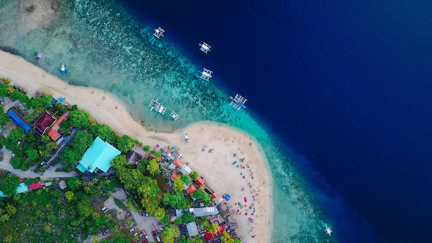 Aerial view of sandy beach with tourists swimming in beautiful clear sea water of the sumilon island beach landing near oslob, cebu, philippines. - boost up color processing. Free Photo