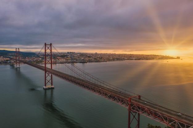 Colpo di vista aerea di un ponte sospeso in portogallo durante un bel tramonto Foto Gratuite