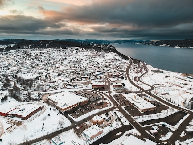 Aerial view of snow covered houses near body of water under cloudy sky during golden hour Free Photo
