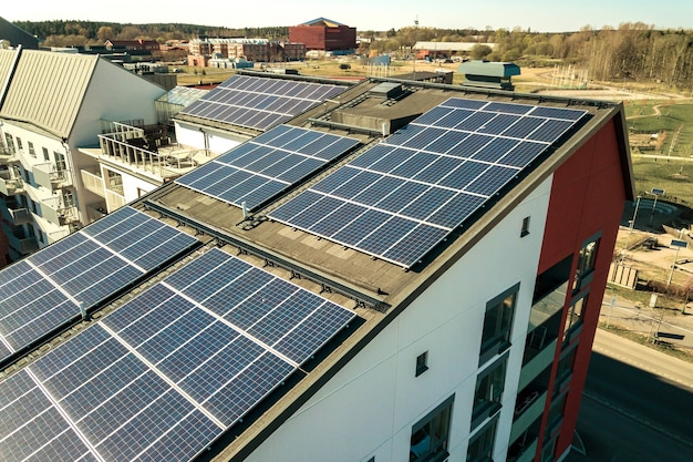 Aerial view of solar photovoltaic panels on a roof top of residential building block for producing clean electric energy. autonomous housing concept. Premium Photo