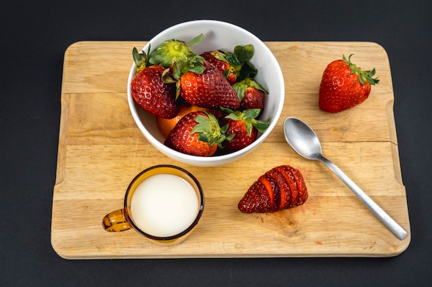 Aerial view of a strawberry cut in a wood with a milk base and a white bowl with more strawberries Premium Photo
