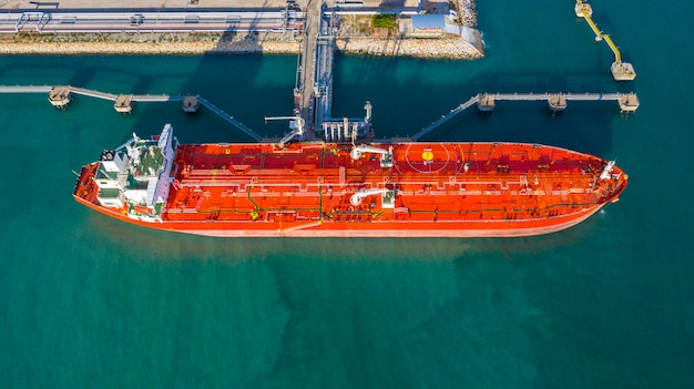 Aerial view tanker ship unloading at port, business import export oil with tanker ship transportation oil from refinery on the sea. Premium Photo